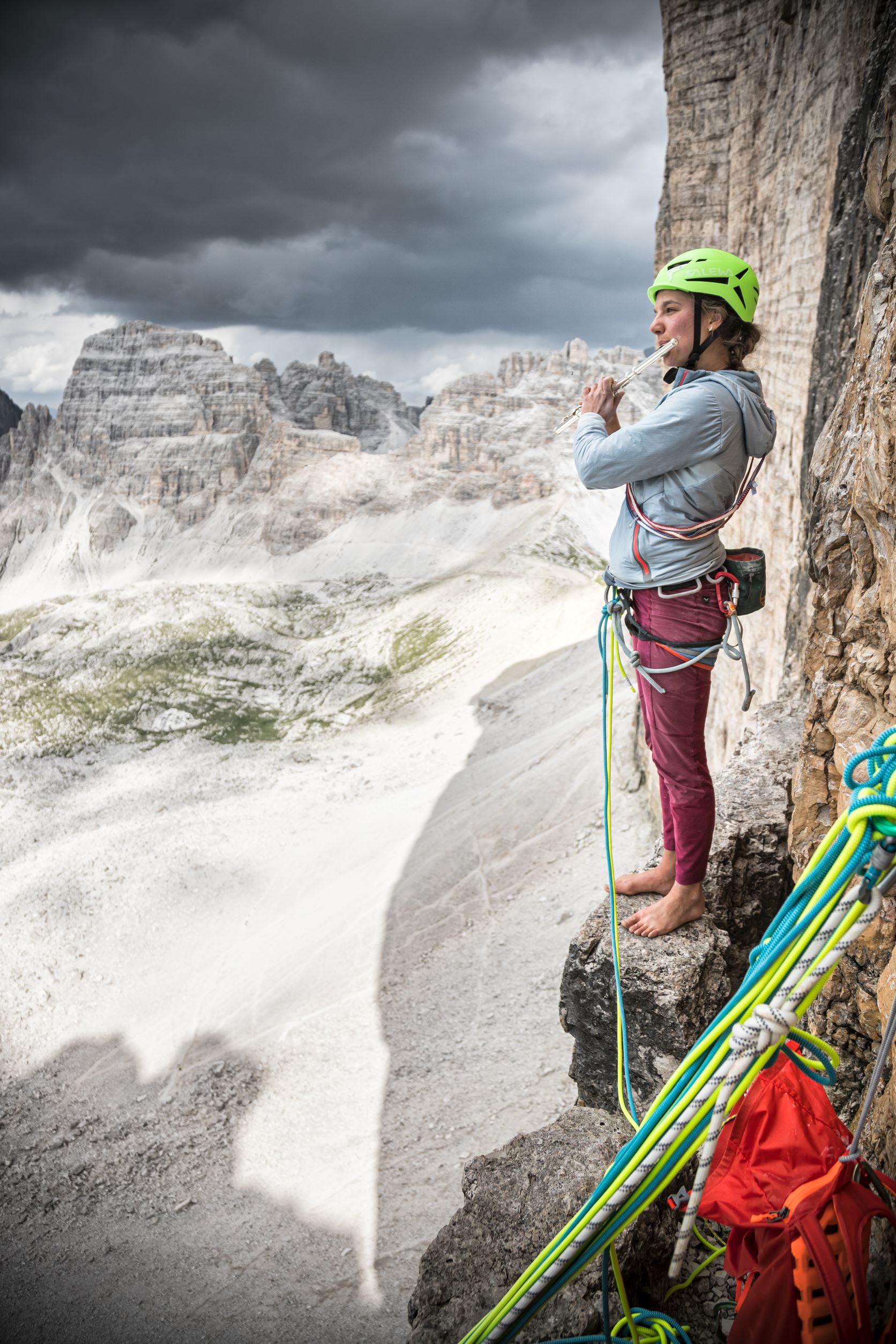 A rock climber plays the flute while standing on a belay ledge in the Dolomites