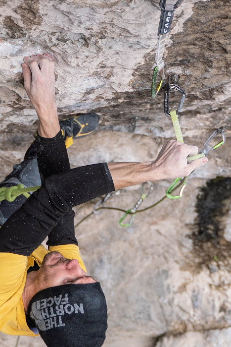 Stefano Ghisolfi clipping some quickdraws while climbing a route