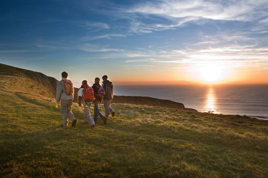 A group of people walking along the coast path as the sun sets over the sea on the horizon