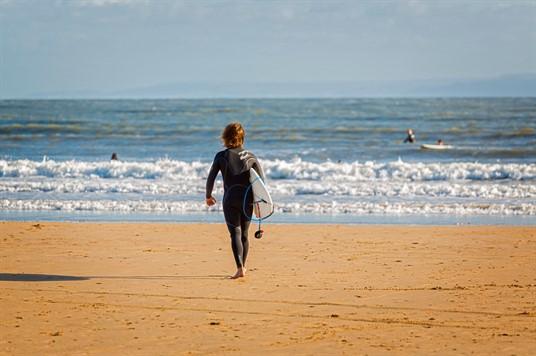 Surfer in wetsuit walking towards the sea