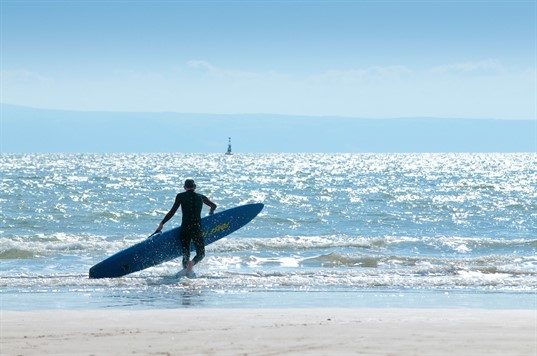 Surfer walking in the shallow sea with board in hand
