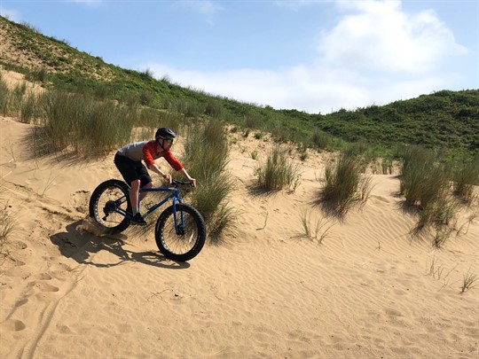 Cyclist riding down sand dune in summer sun