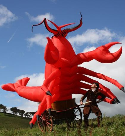 A giant inflatable lobster being pulled in a cart