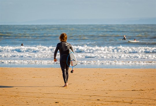 Surfer in wet suit walking towards sea with board in hand