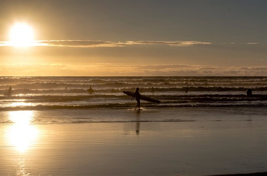 Surfer walking with board in hand as the sun sets over the ocean behind them
