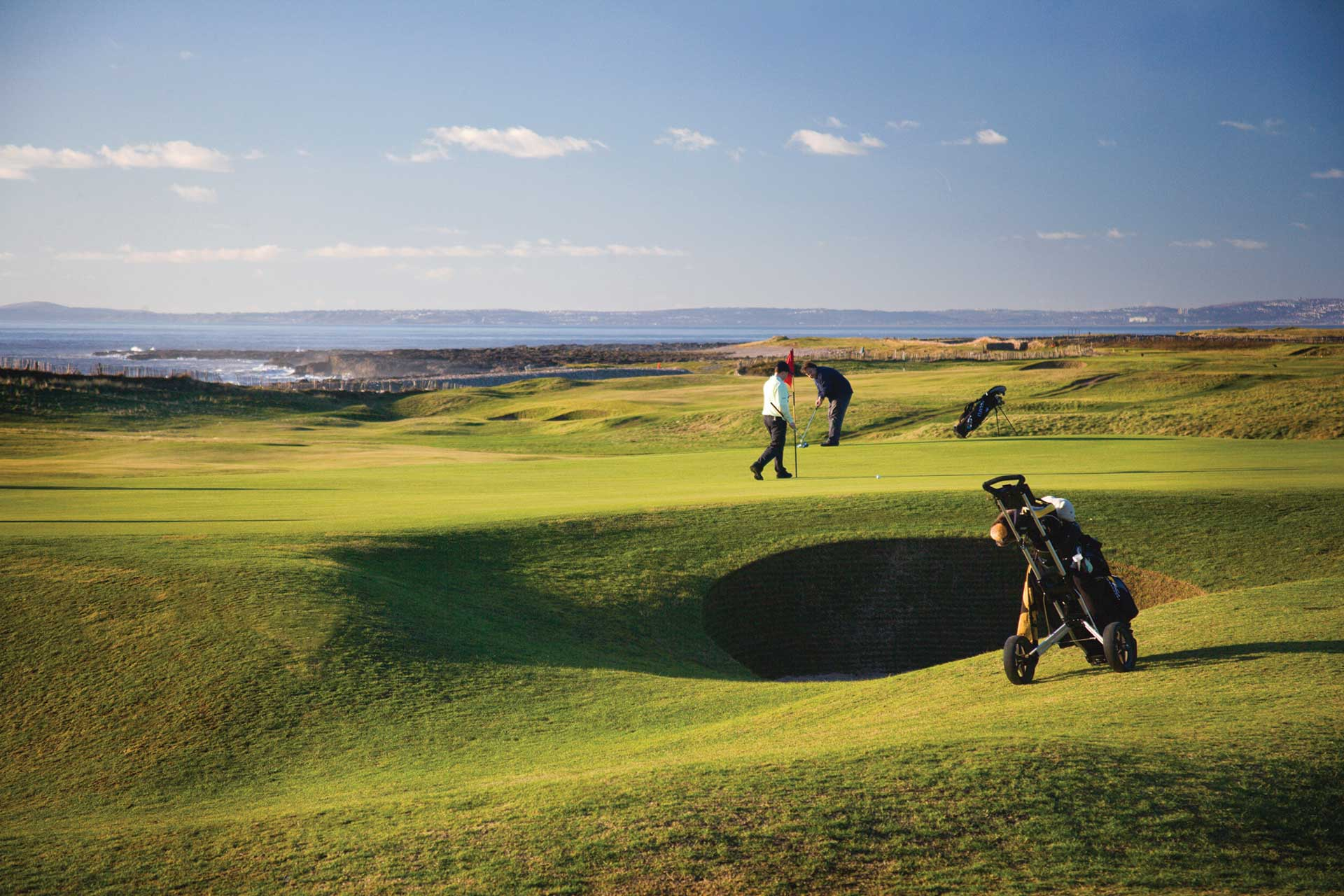 The rolling terrain and golf green at the Royal Porthcawl Golf Club