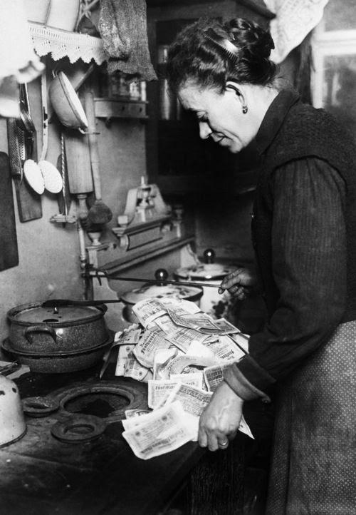 Kobieta rozpalająca kuchenkę używając do tego pieniędzy