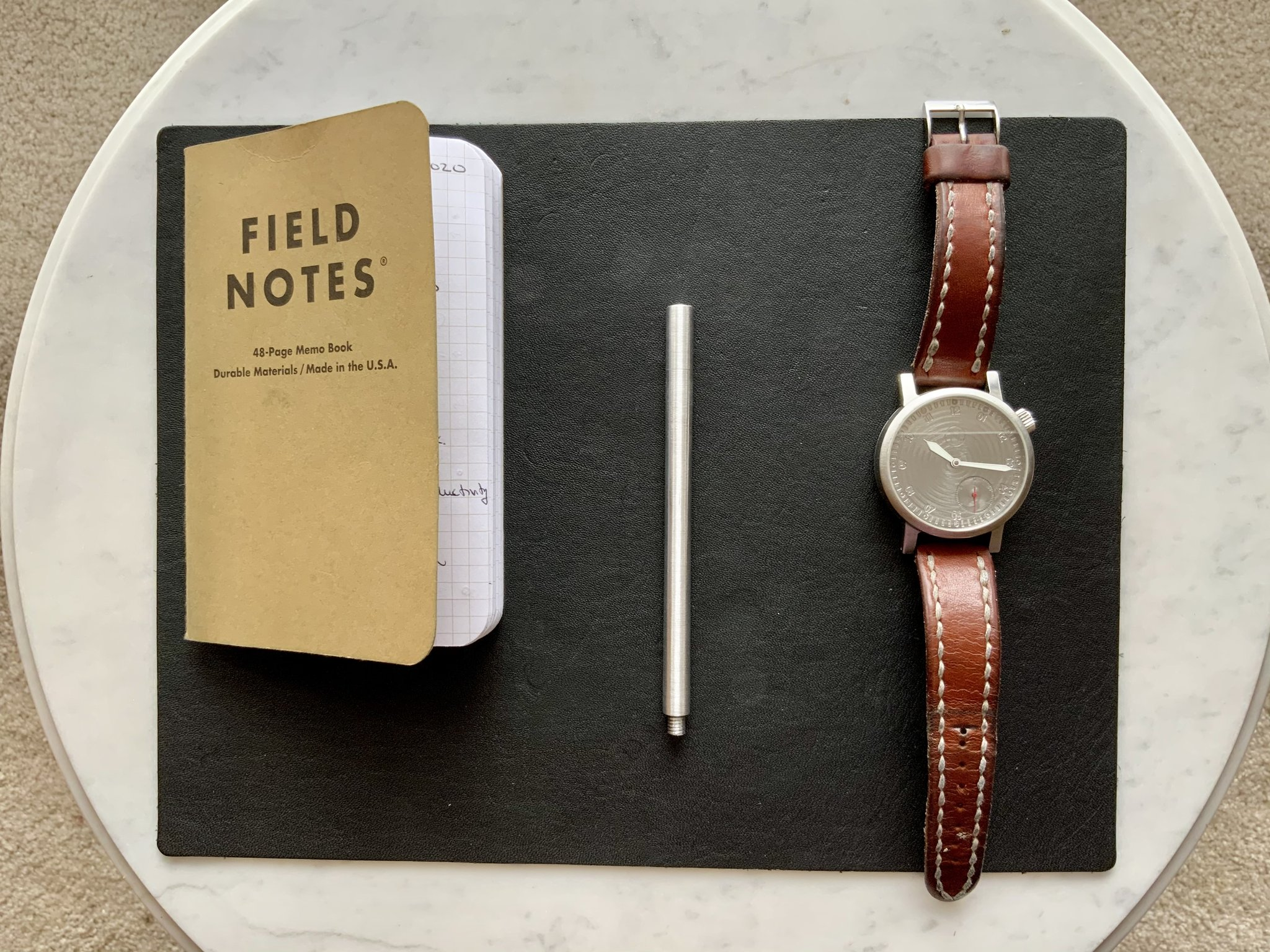 Novo pen, watch and a notebook on table.