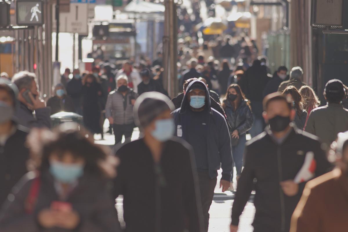 crowds of people walking down a street wearing masks in the uk