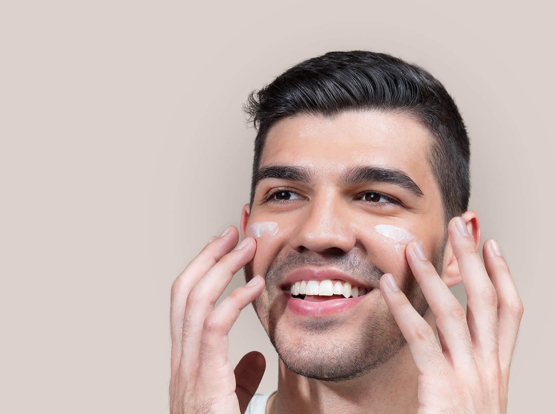 Man putting cream on his face.