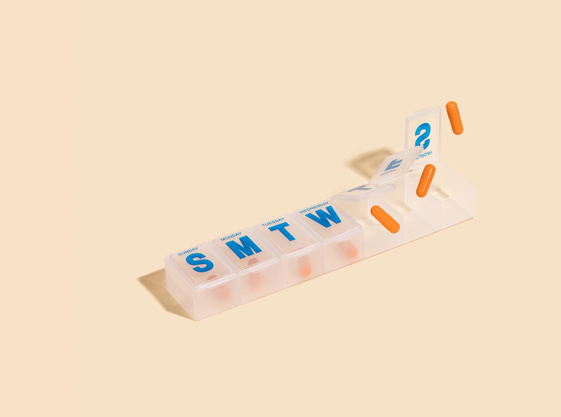 Pill box with orange pills inside.