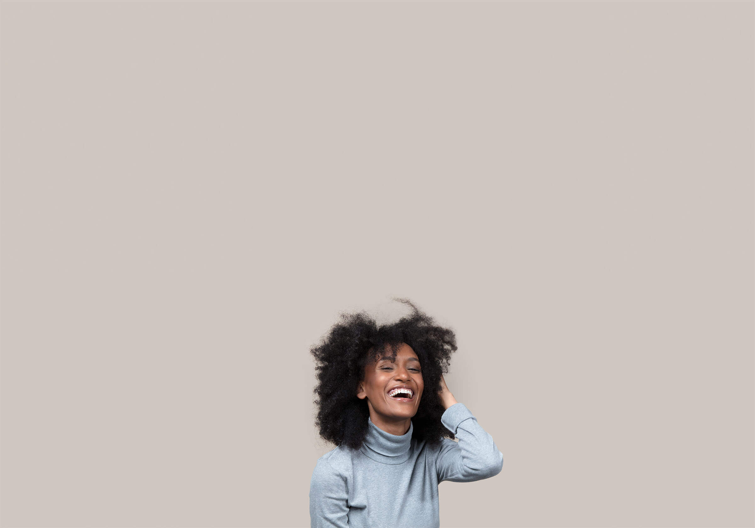 Woman laughing and brushing her hair.