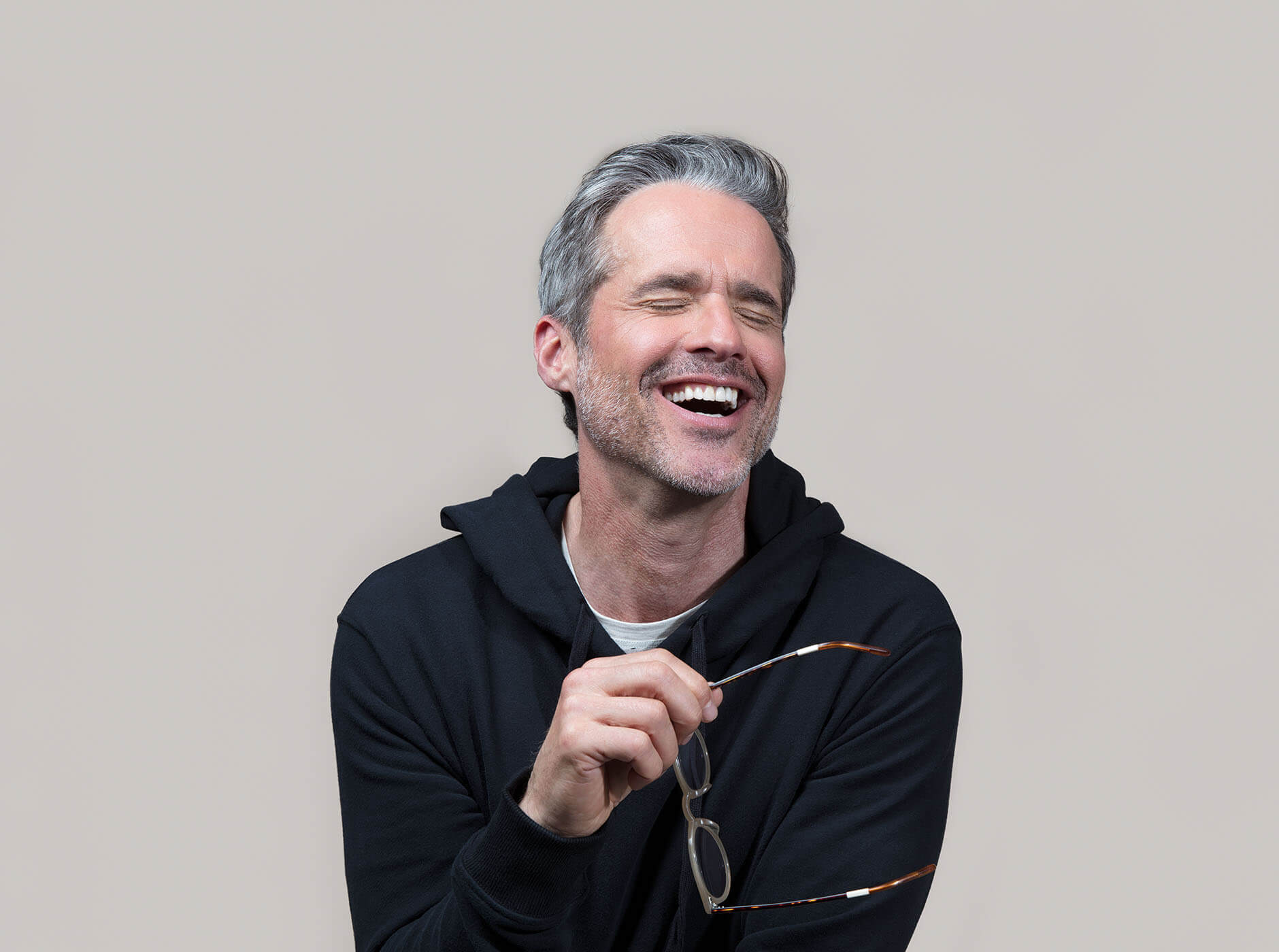 Man holding glasses laughing.