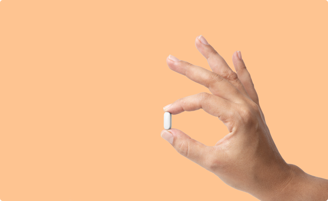 Blister pack of pink and white pills on orange background.
