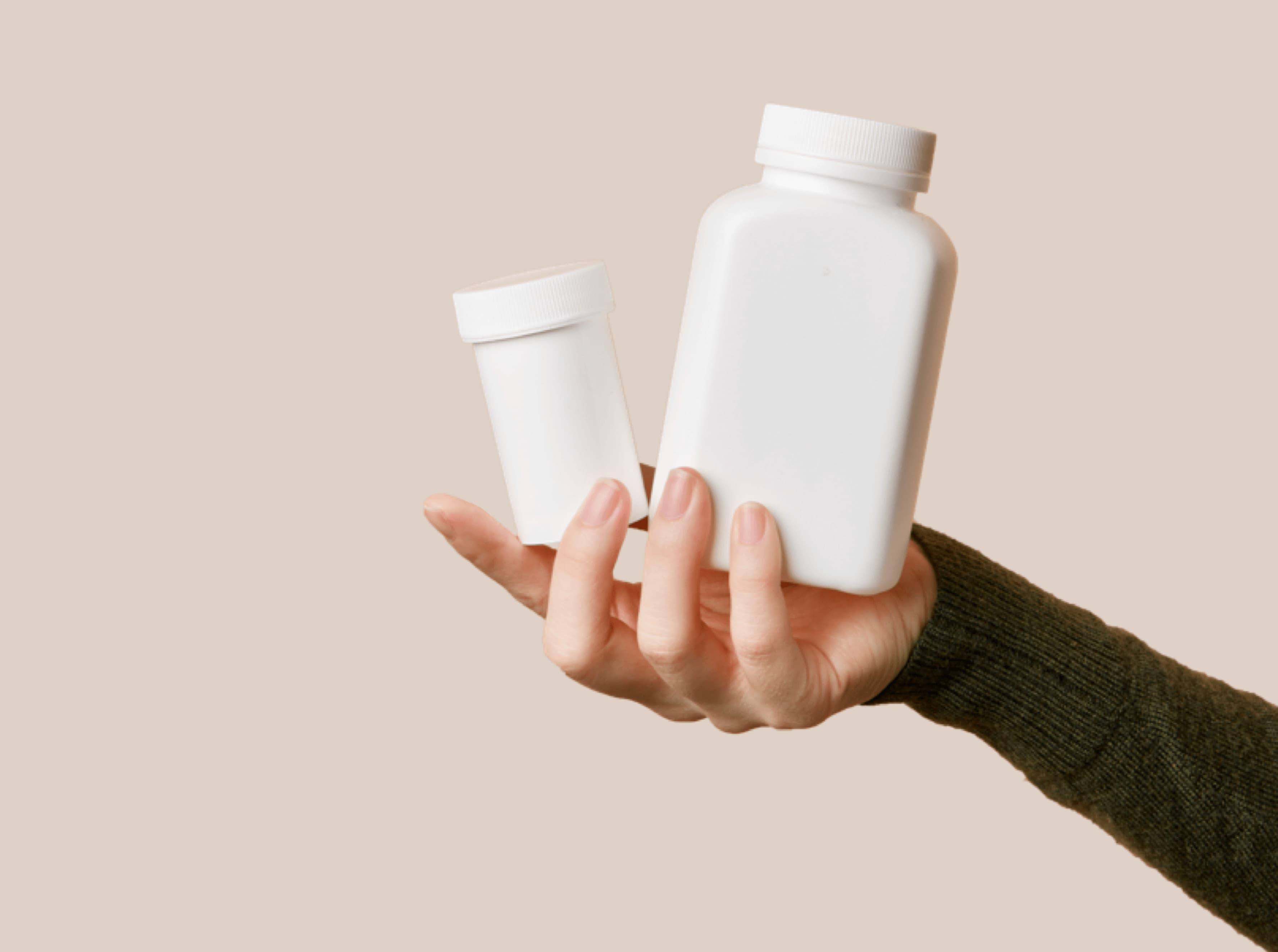 Hand holding white pill bottles