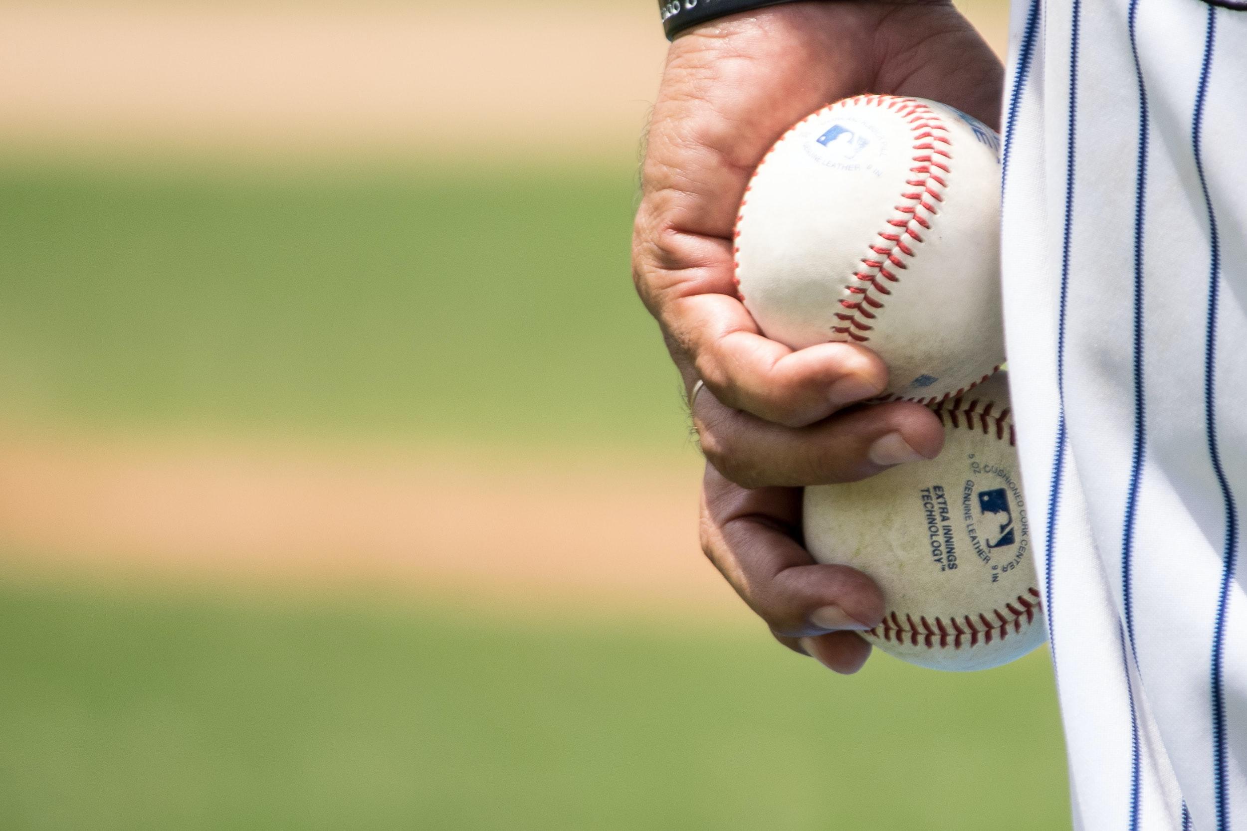 Mans hand holding to Major League Baseballs