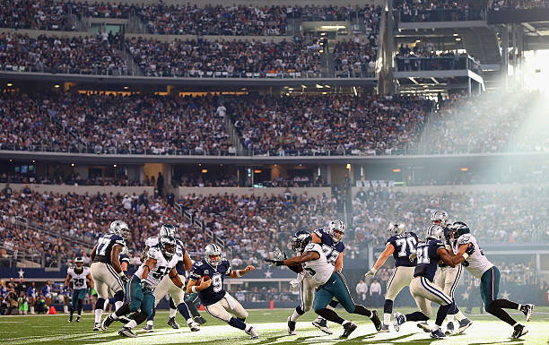 Tony Dallas Cowboys player Romo #9 holds the ball under pressure from the Philadelphia Eagles at Cowboys Stadium