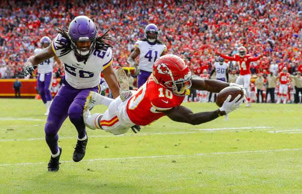 Kansas City Chiefs player Tyreek Hill #10, diving to the goal line followed behind by Minnesota Vikings defensive player Trae Waynes #26
