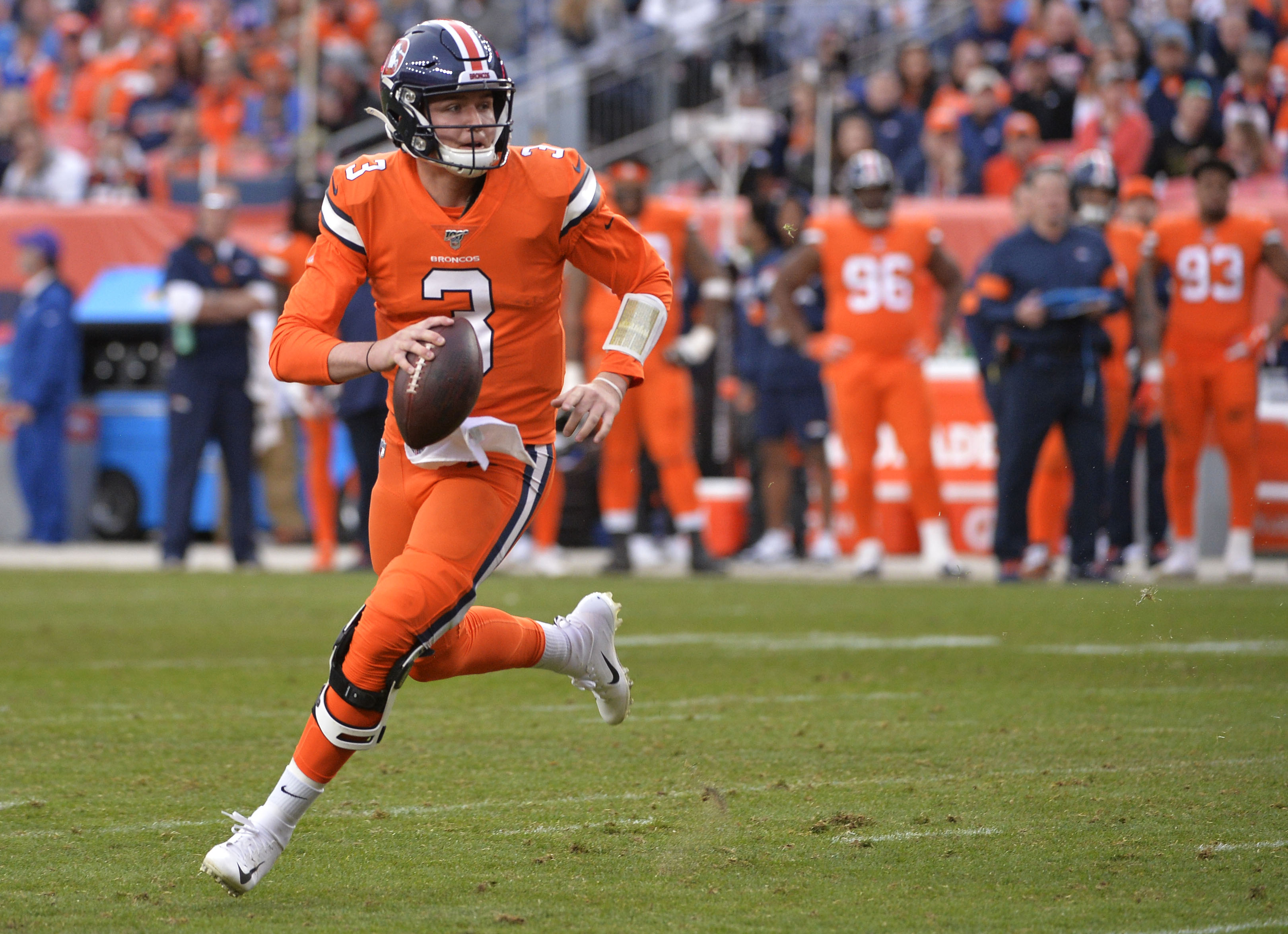 Denver Broncos quarterback player, Drew Lock, running down NFL field holding football