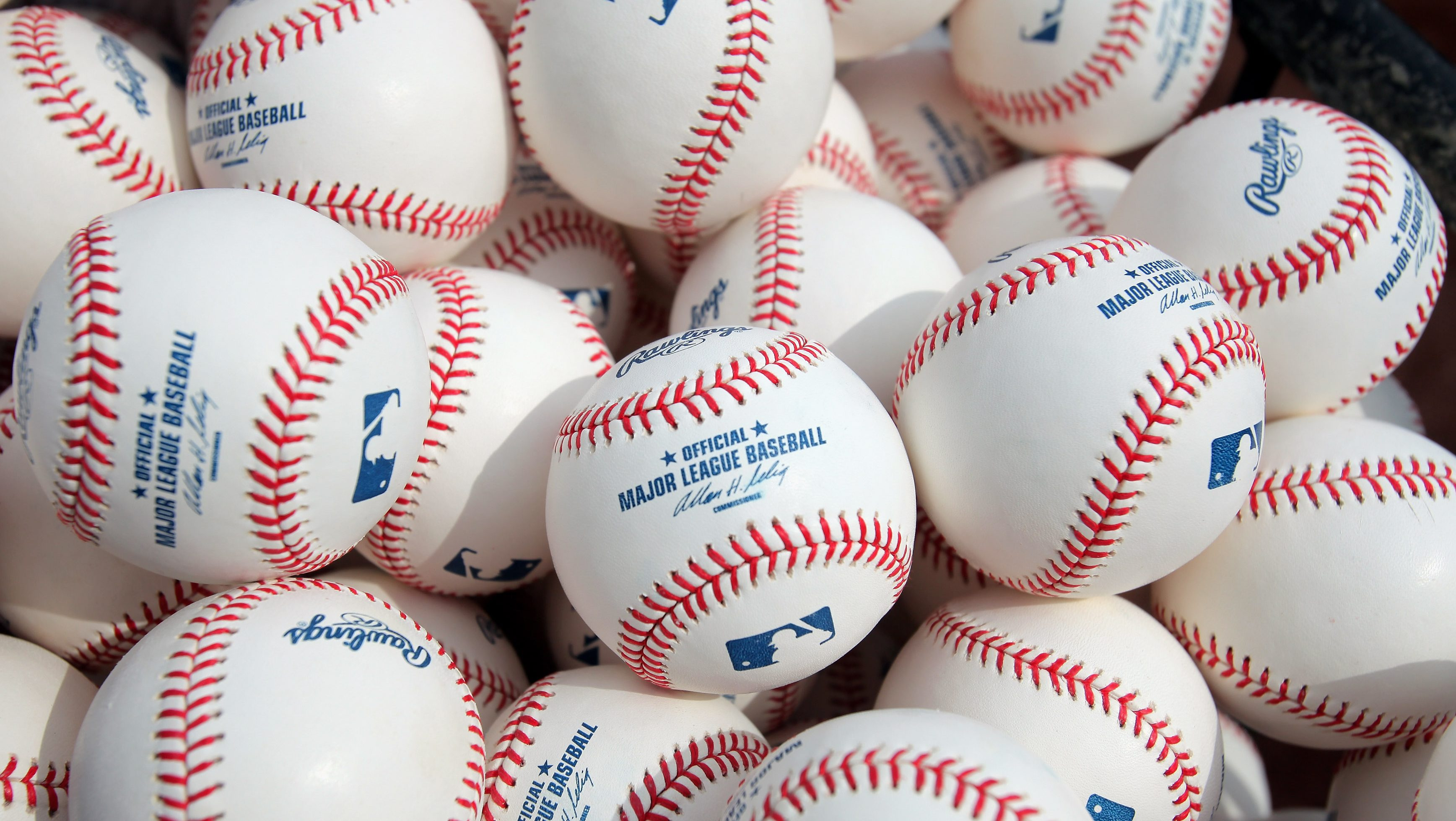 "Pile of MLB baseballs with the words ""Official Major League Baseball"""