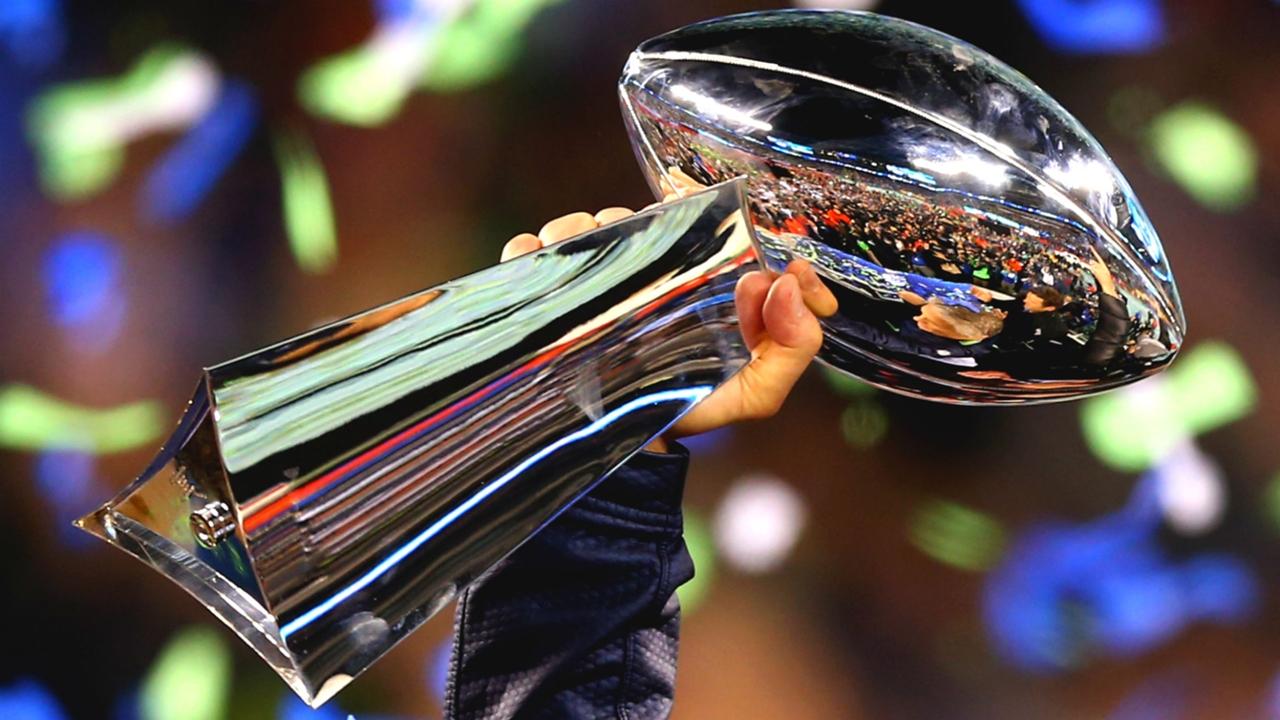 Hand holding up NFL Super Bowl Trophy