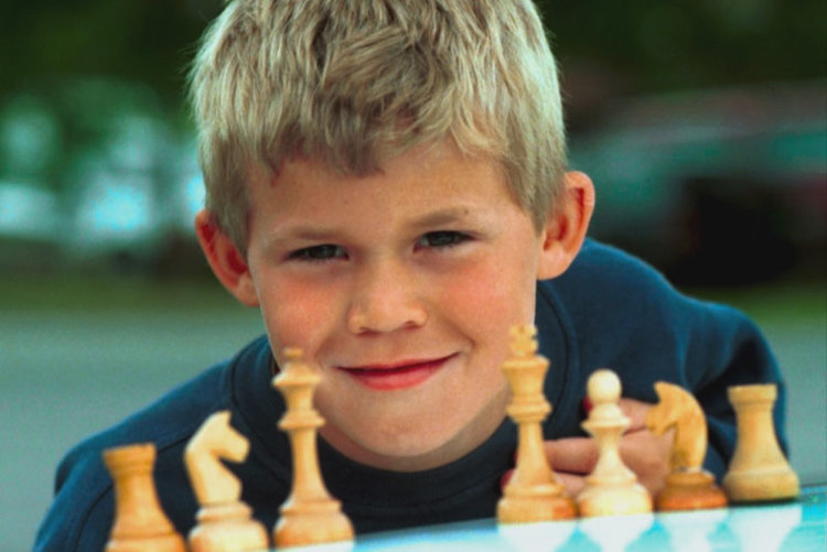 An image of Magnus Carlsen as a child in front of a Chess Board