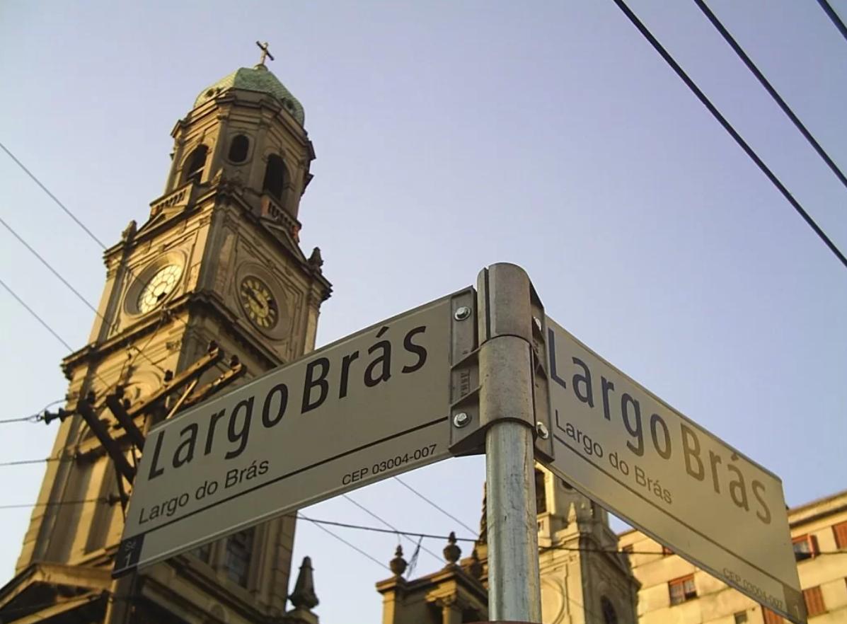 Placa de rua do largo do Brás com uma igreja atrás