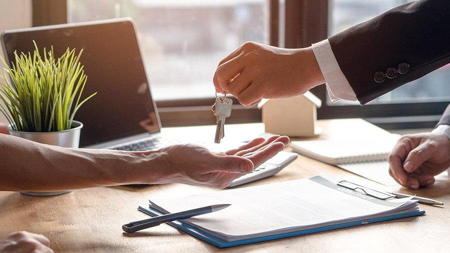 Corretor entregando a chave ao comprador do imóvel
