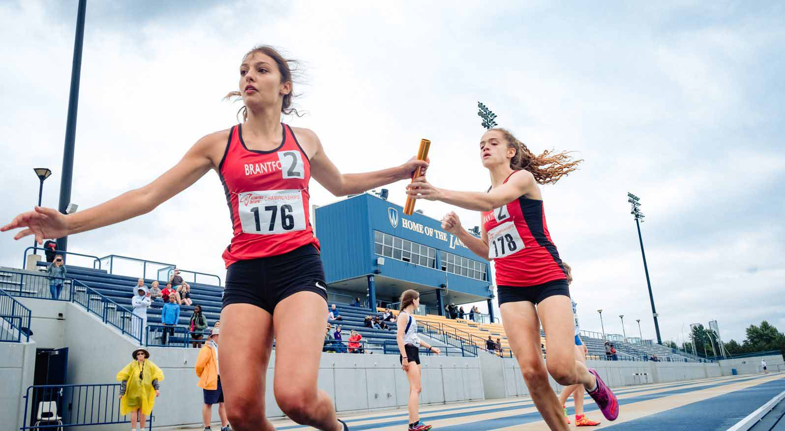 Athletes in an Athletics Ontario relay race pass off a baton