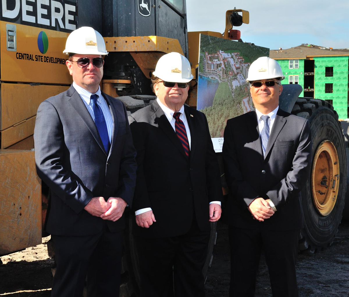 Picture of executive team with a bulldozer.