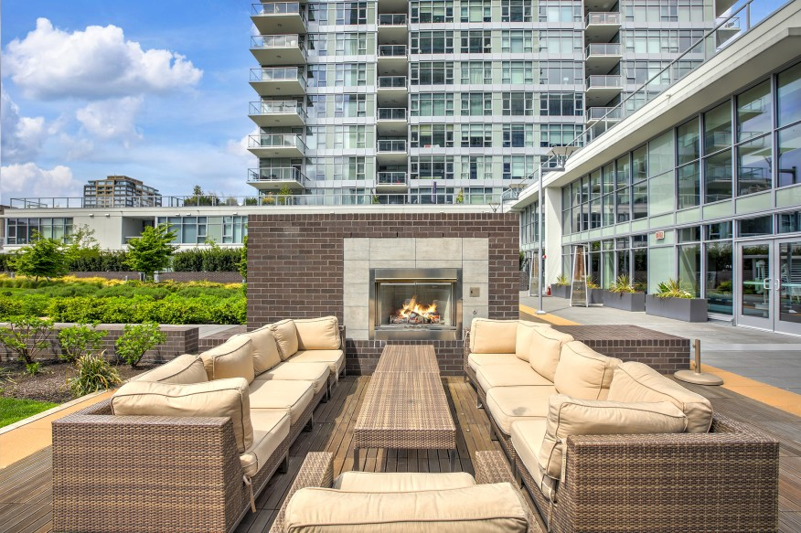 Contemporary open-air park with spacious lounge area equipped with wicker furniture and brick fireplace. Northwest, USA