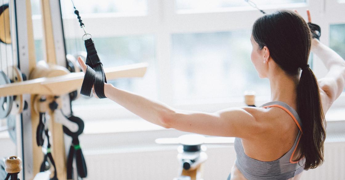 Woman at a fitness studio using a Pilates machine