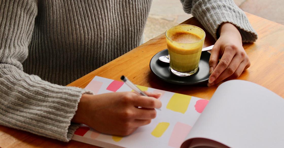 Woman drinking a golden milk latte while journaling