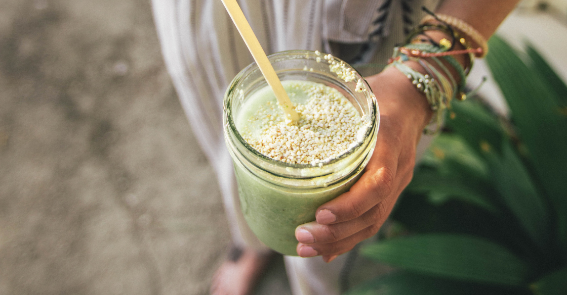 Woman drinking a glass of green juice