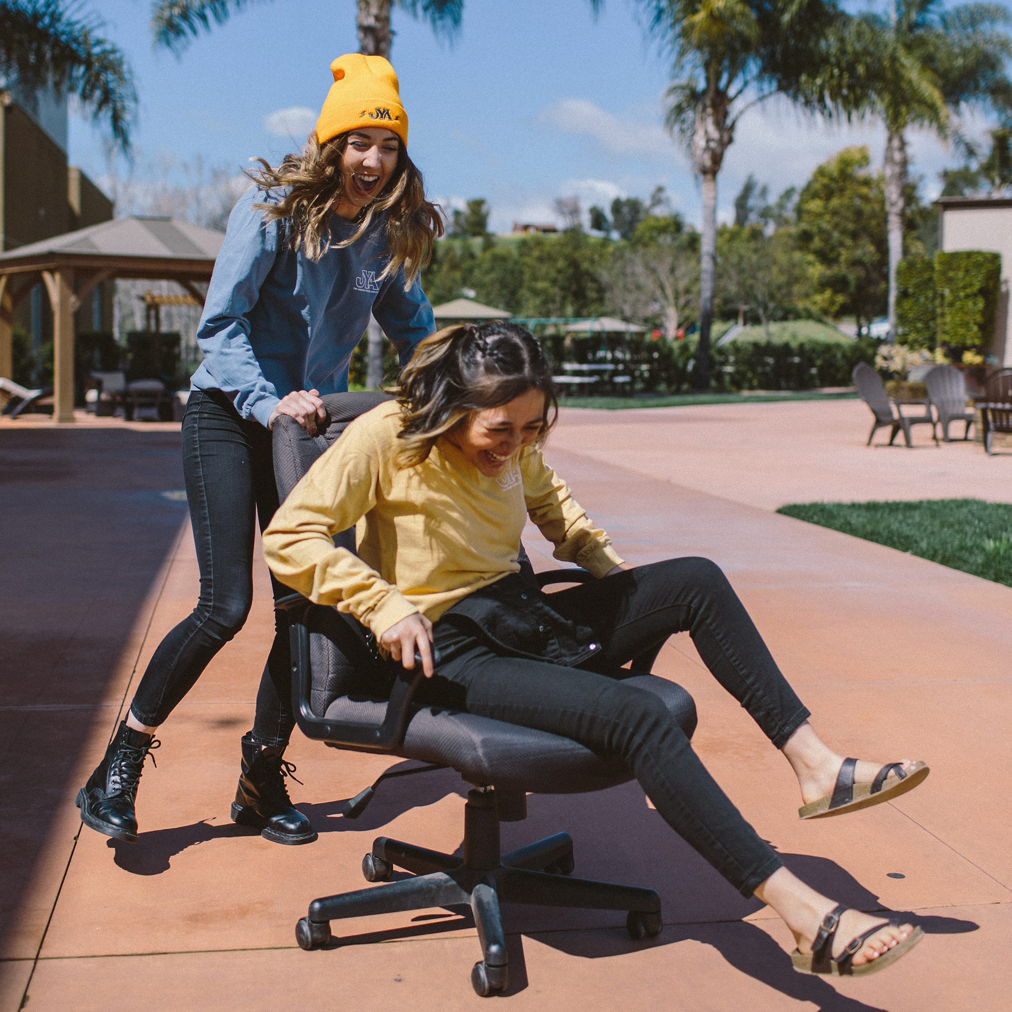 Woman pushing another woman on a desk chair having fun