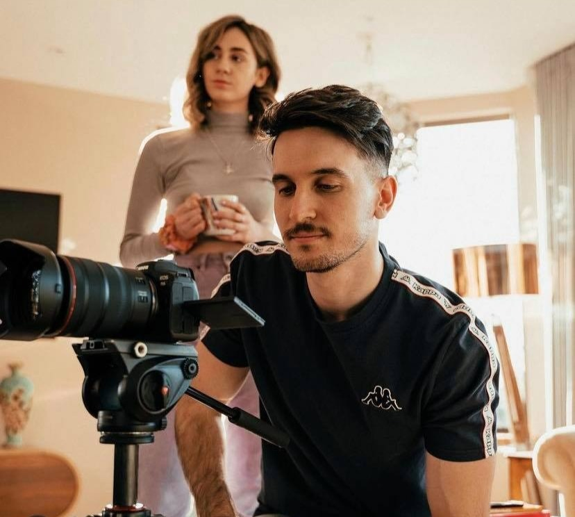Man and a woman looking at a subject beyond a camera.