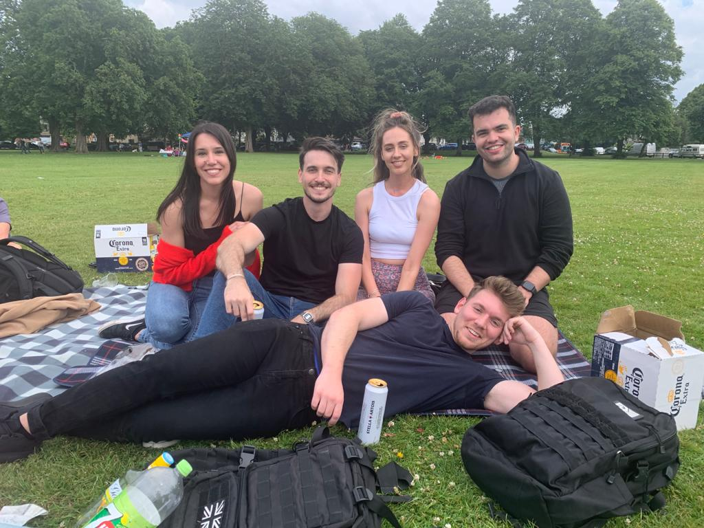 Aura Ads team laying in the park with each other.