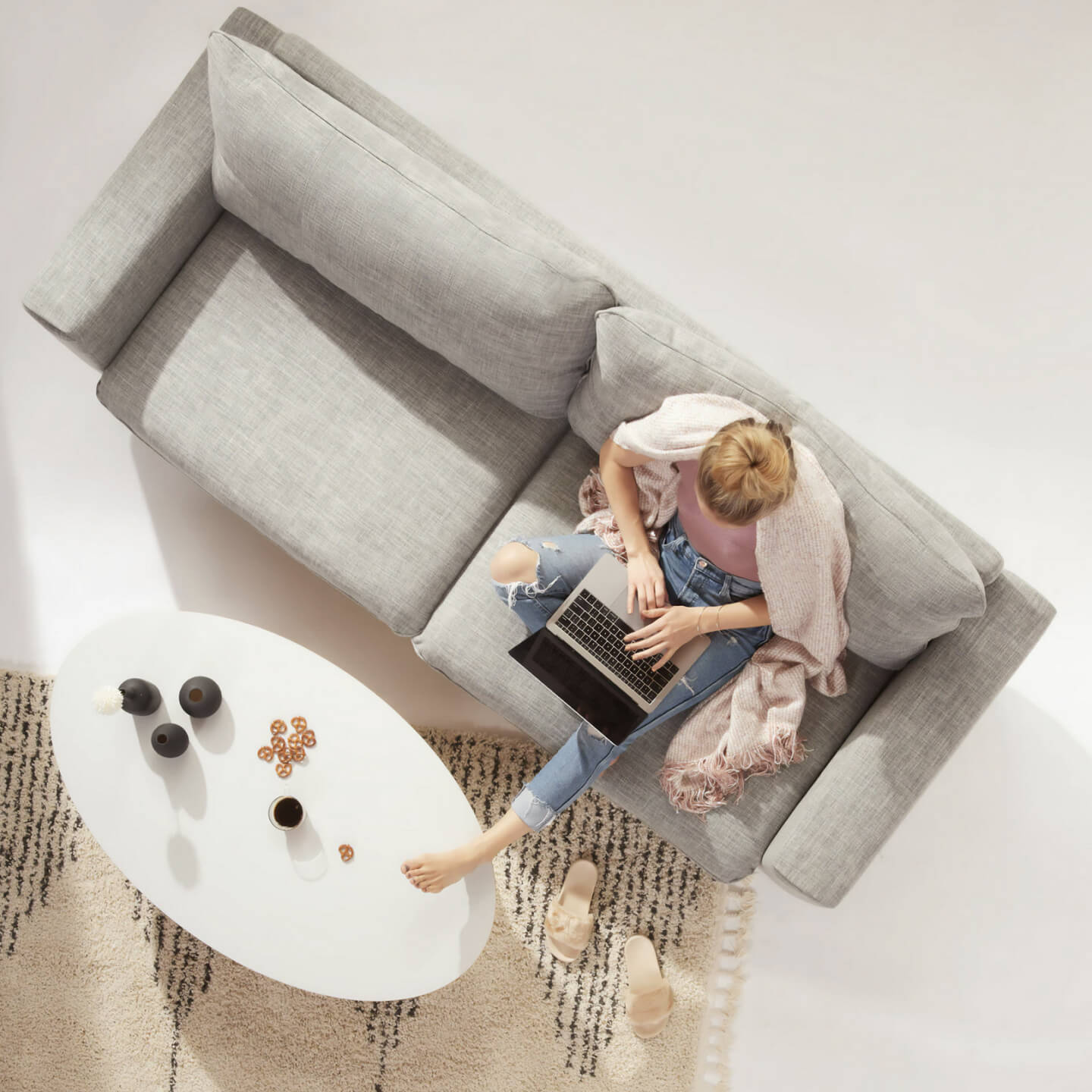 Girl on computer sitting on grey sofa white mid mod coffee table
