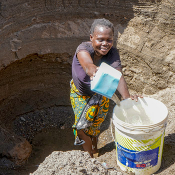 A woman fetching water from a hand dug well
