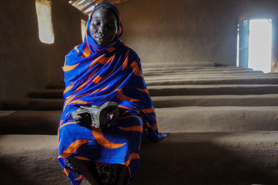 Sudanese refugee sitting on a mud pew with her Bible