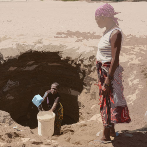 Internally displaced women fetching water out of a hole dug into a dry river bed in Kakuma, Kenya