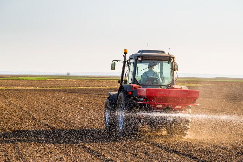 Traktörle gübreleme yapan çiftçi.