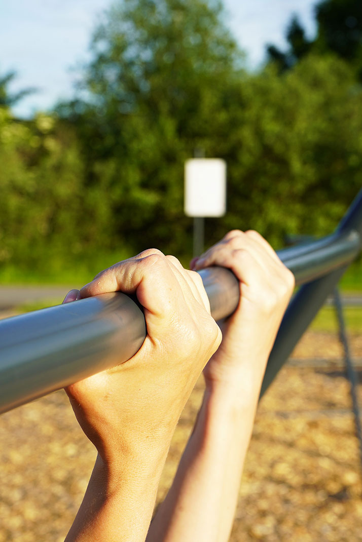 Close up of person using pull up bar
