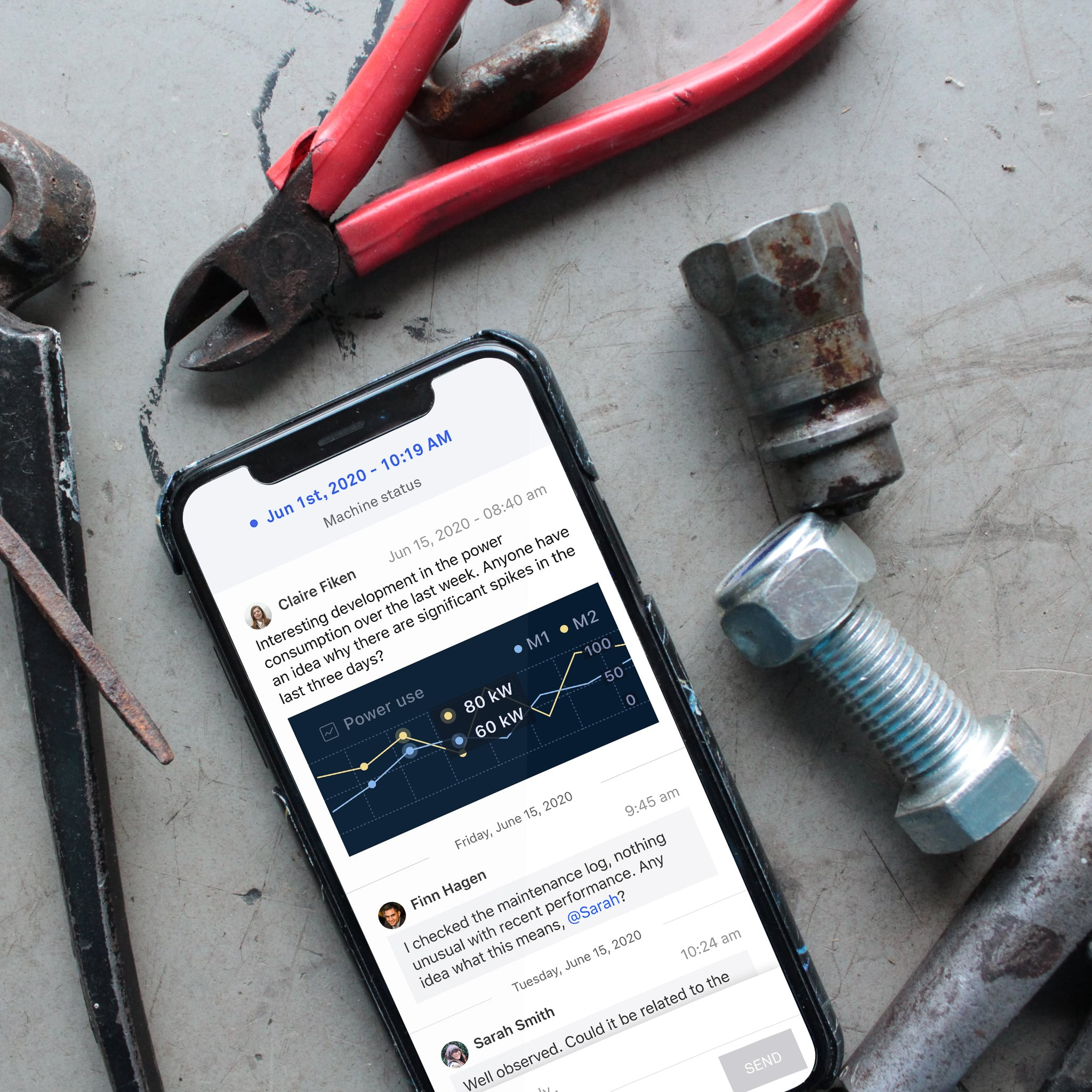 Clarify app interface displaying comments on an iPhone laying beside tools at unpolished industrial desk