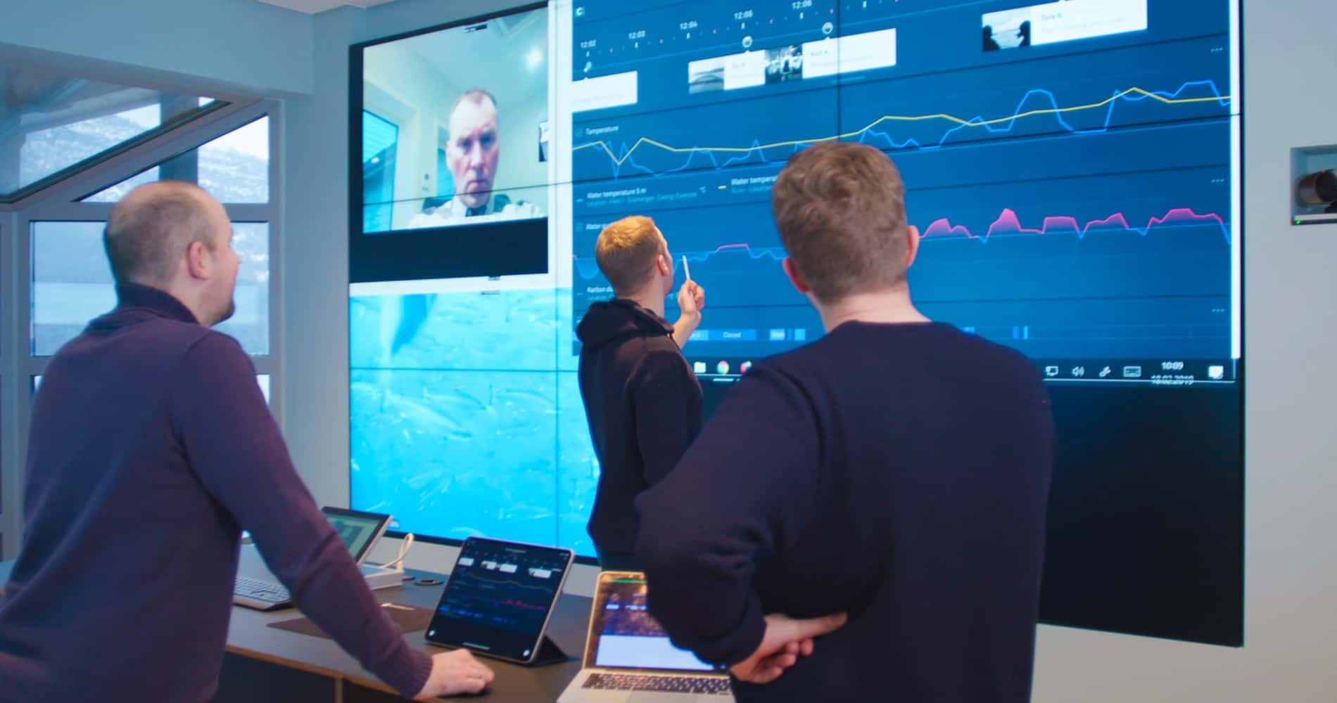 Three men looking at Clarify graphs displayed on a big screen at Eide Fjordbruk office