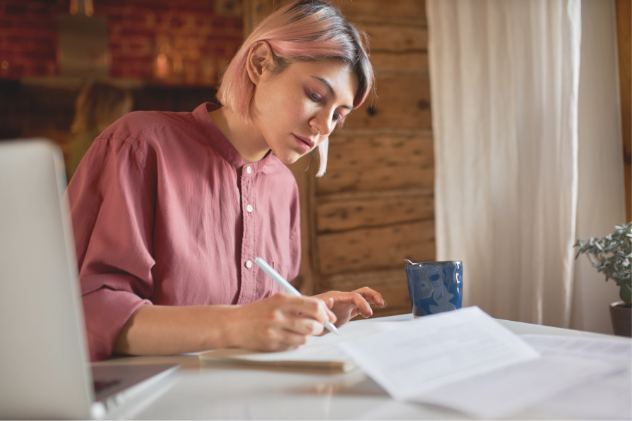 pensive young lady thinking of sympathy words while writing condolence message