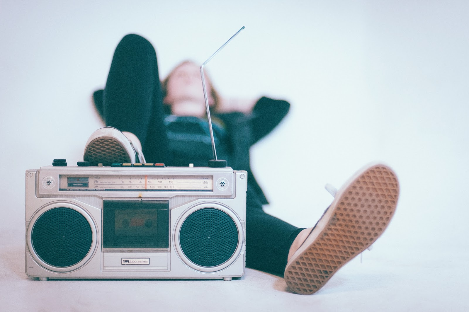 a young female lounges on a bed casually with one foot resting on top of a silver AM/FM radio playing her favorite music