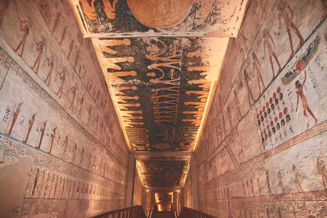 Illuminated stairway inside tunnel of Egyptian pyramid with hieroglyphics along walls and ceiling