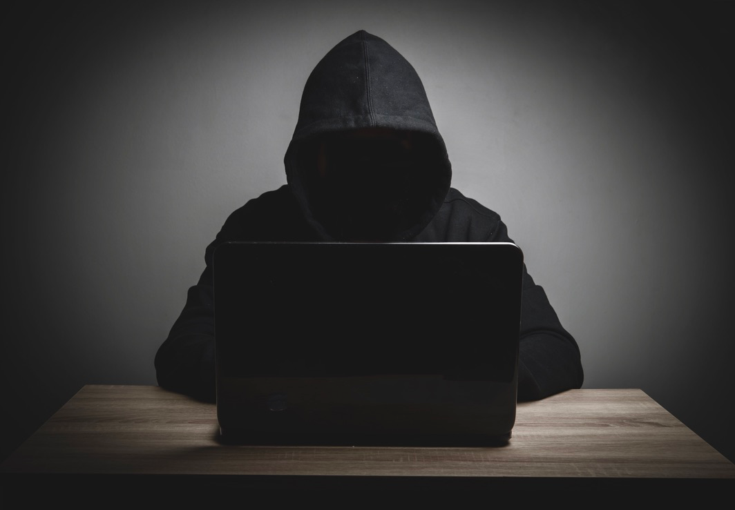 Hooded hacker accesses dark web with laptop