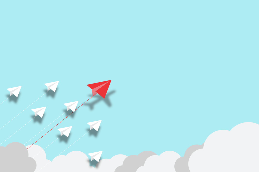 red paper airplane leads ahead of other airplanes